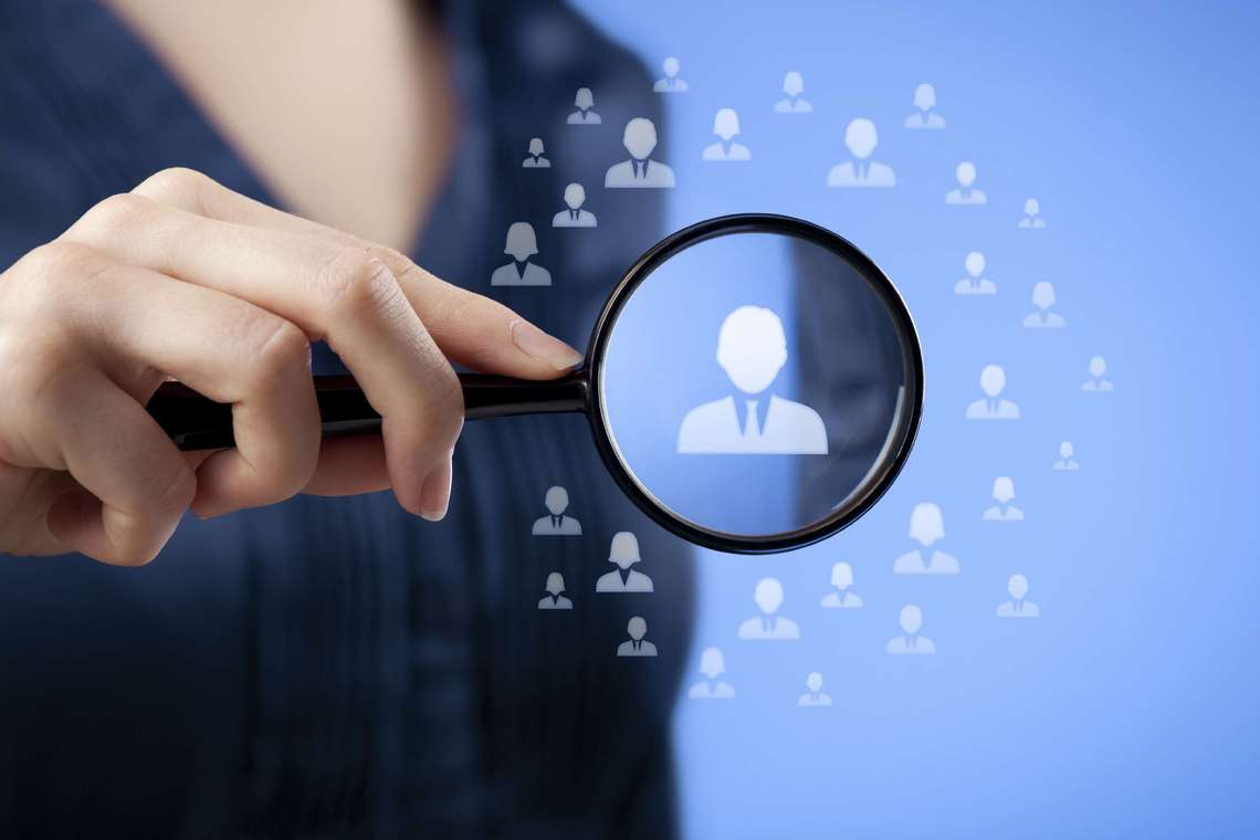 Recruiter magnifying glass for qualified candidates.