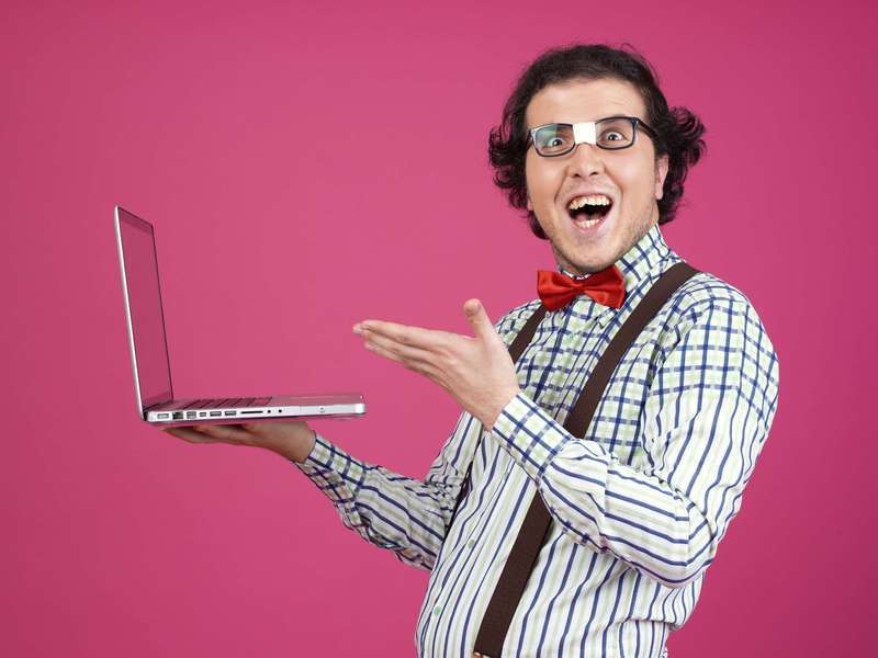 Nerd on pink background with laptop.