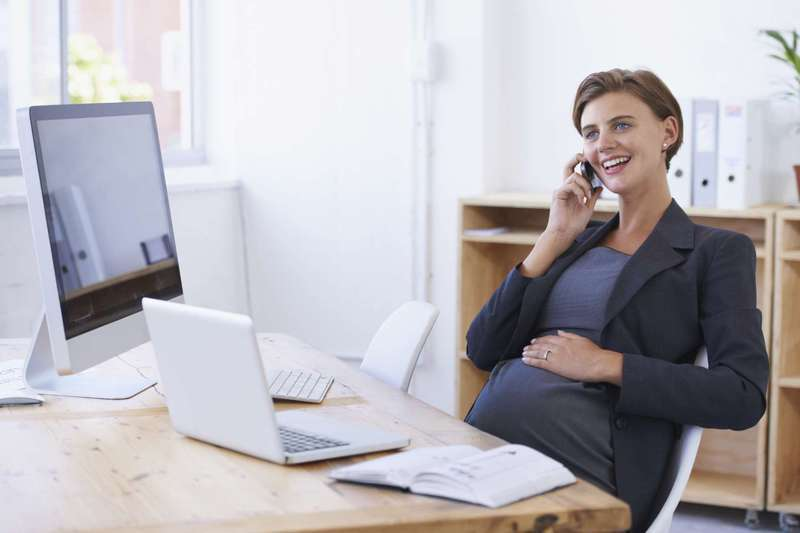 Pregnant woman at work on phone